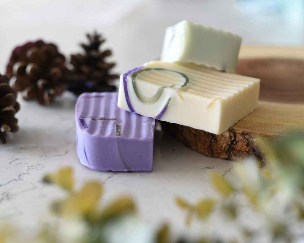 Mini Lifestyle Tabletop Photo of purple and cream handmade soap with pinecones and wood