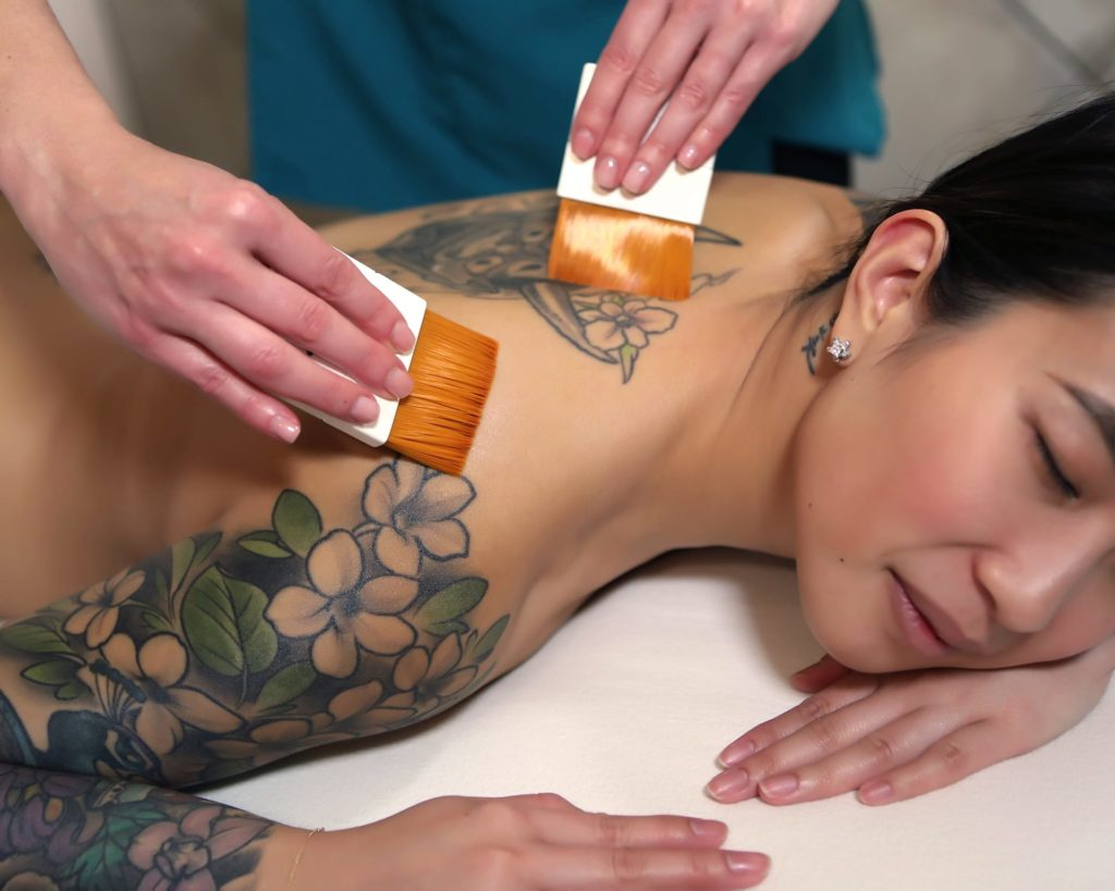 Lifestyle photo of woman with tattoos lying on stomach while hands massage her back with brushes