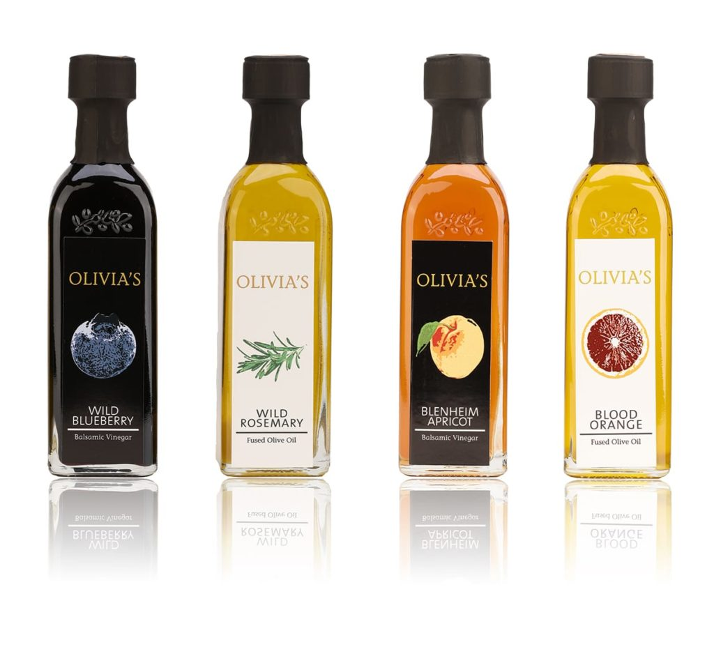 Product photo on white background with shadow of 4 yellow, black and orange olive oil and balsamic vinegar bottles