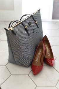 Mini Lifestyle photo of calvin klein red high heel shoes with striped bag on white tile floor by door