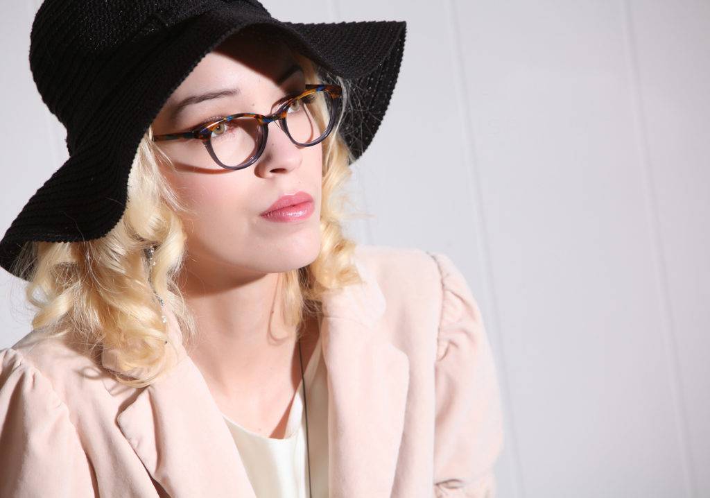 product photo with model wearing a black hat and pink jacket and glasses