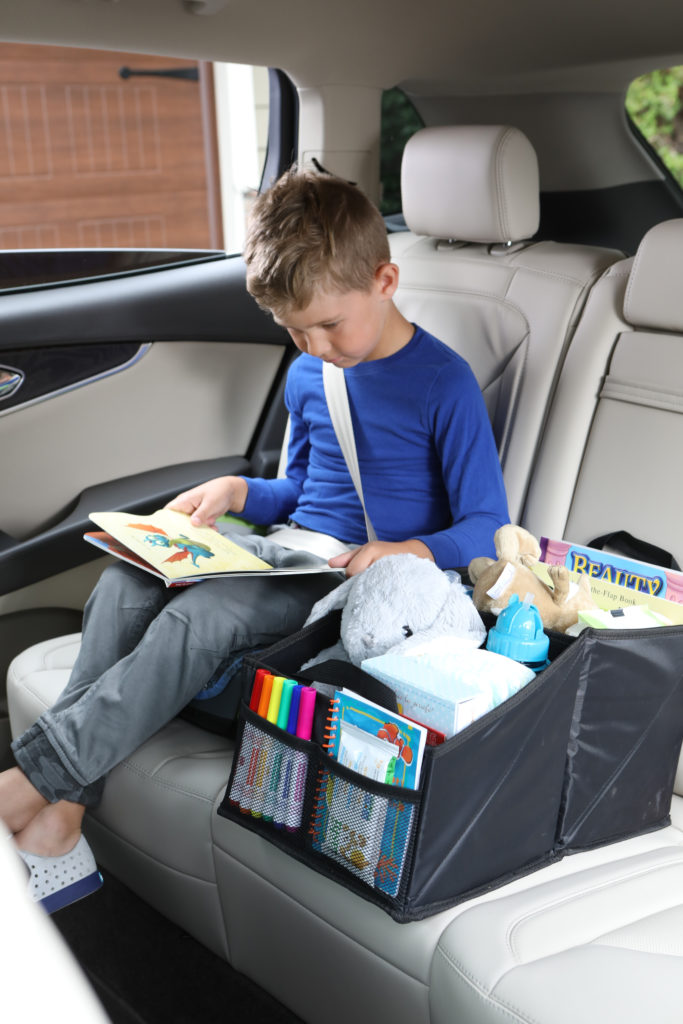 Lifestyle photo of boy in blue shirt reading a book in a car with toy box product