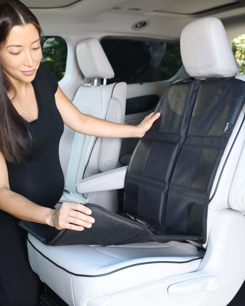 Product photo of woman wearing black demonstrating baby car seat mat