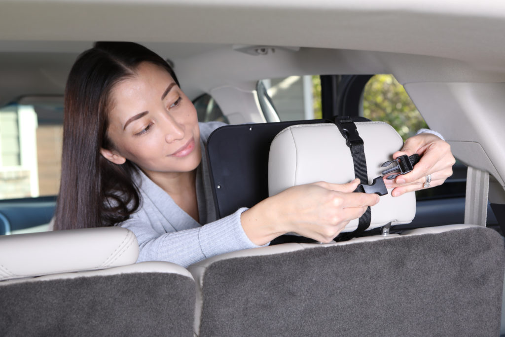 Lifestyle photo of woman in car demonstrating buckle of baby car product