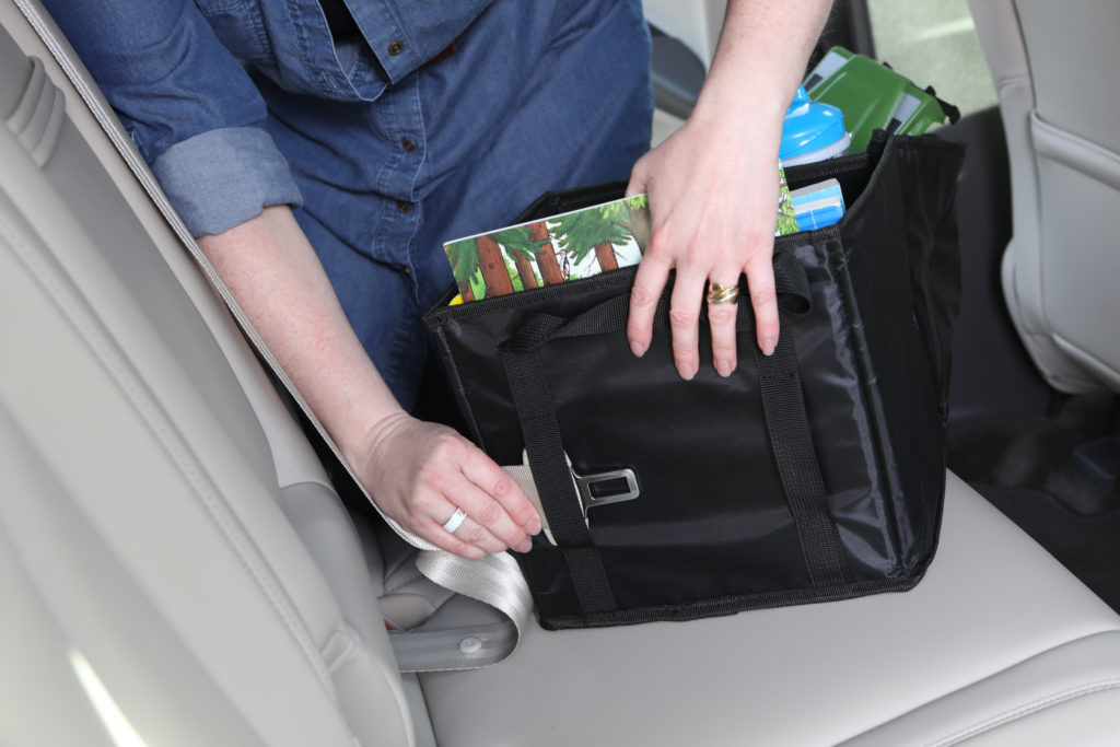 Lifestyle photo of hands demonstrating seat belt holder of child car product
