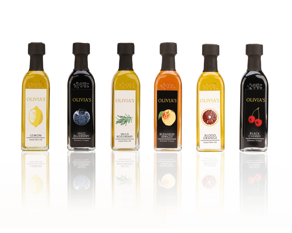 Product photo on white background with shadow of row of yellow, black and orange olive oil and balsamic vinegar bottles
