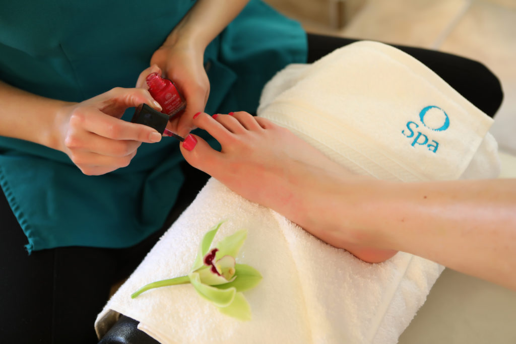 lifestyle photo of pedicure with red nails on a white towel with flower