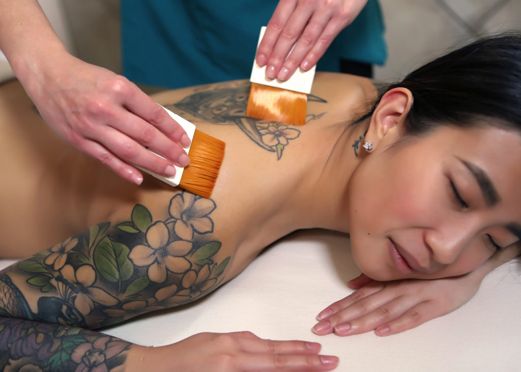 lifestyle photo of woman with tattoos lying on stomach with hands massaging back with brushes