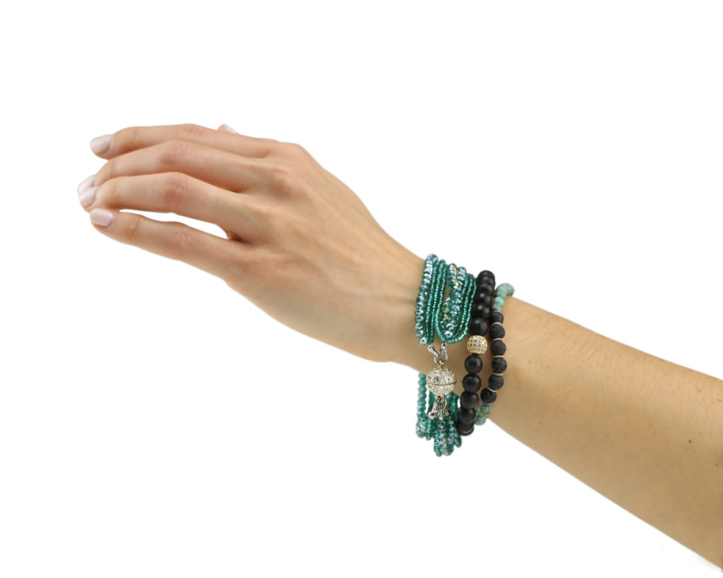 Hand model product photo on white background of hand wearing turquoise and black beaded bracelets