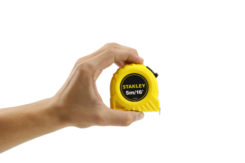 Hand model product photo on white background of hand holding a yellow stanley measuring tape