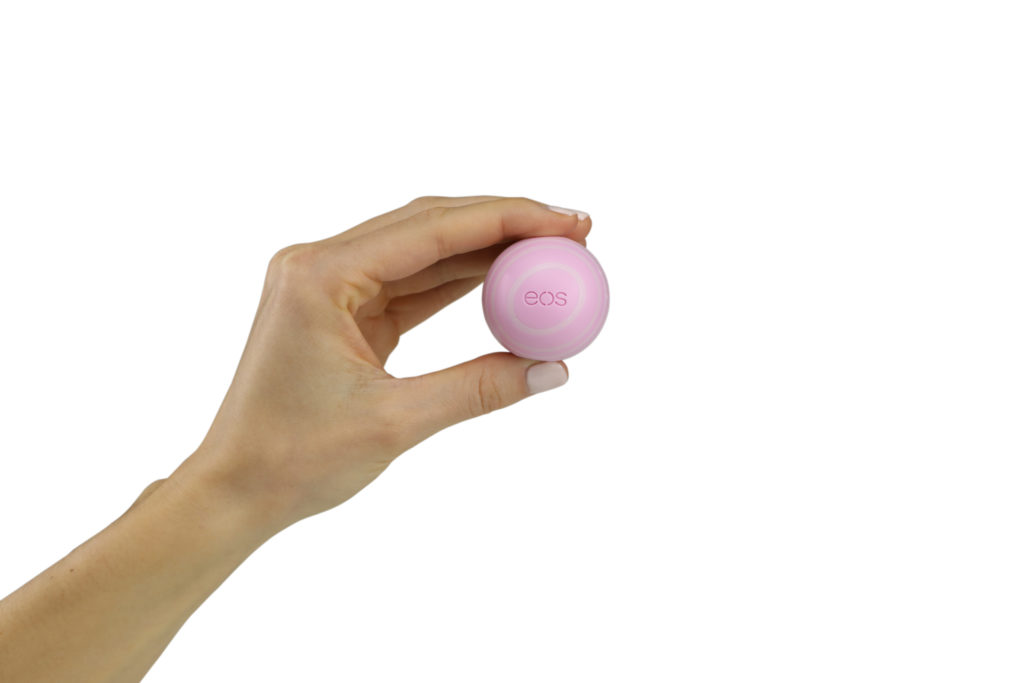 Hand model product photo on white background of hand holding a pink eos ball