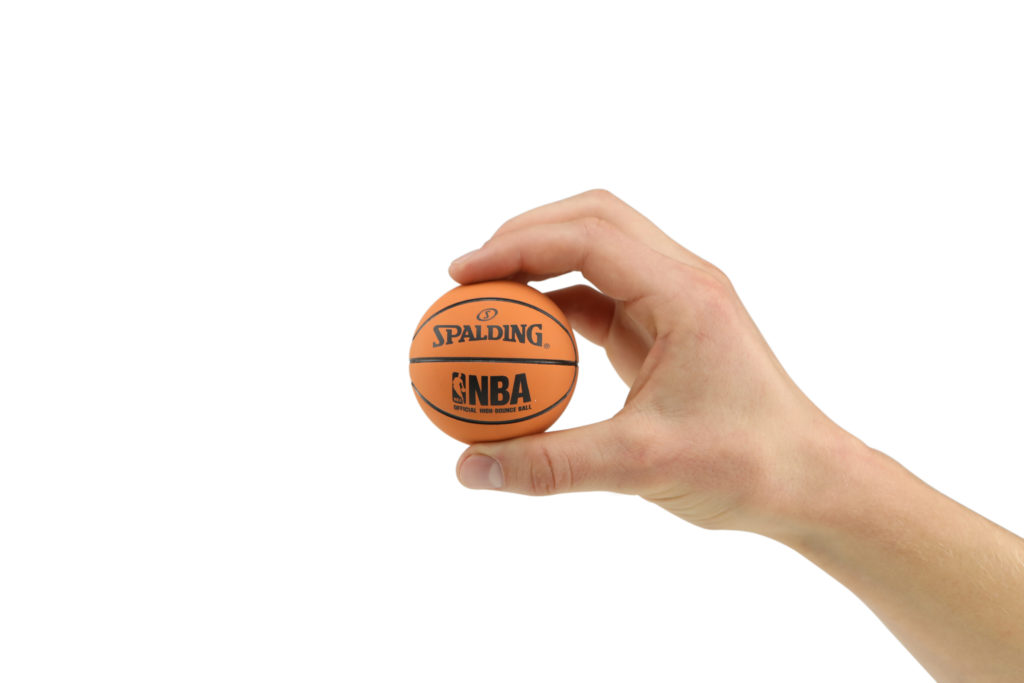Hand model product photo on white background of hand holding a mini orange basket ball