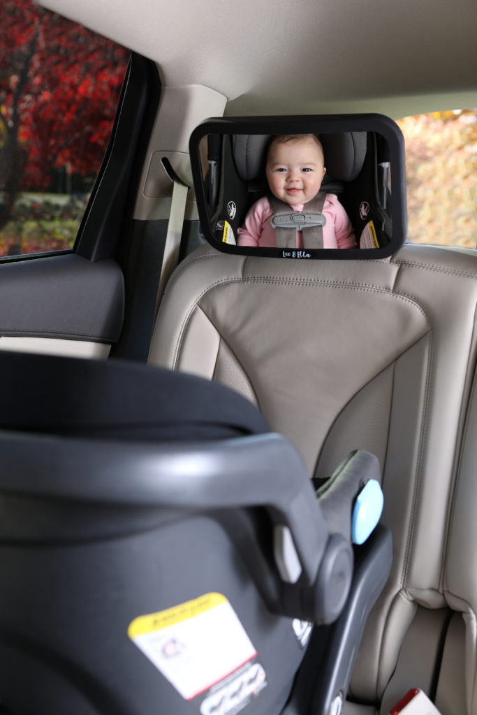 Lifestyle photo inside a car with a baby's face in a car mirror