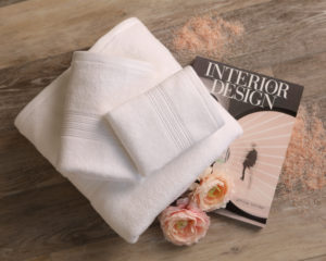mini lifestyle photo of white towel and interior design magazine wooden tabletop product photograph