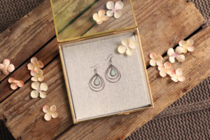 mini lifestyle photo of jewelry in box with peach flowers on wooden tabletop product photograph