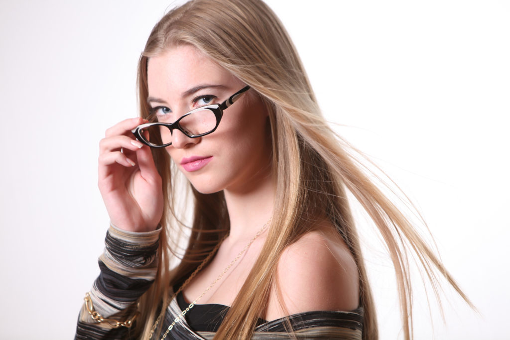 Lifestyle product photo of blond woman wearing glasses and a striped shirt with jewelry on a white background
