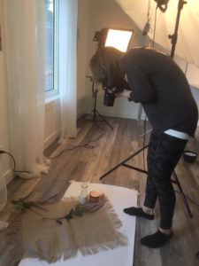 behind the scenes photo of taking a picture of a lifestyle set up of cream and burlap in front of window