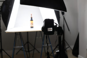 behind the camera photo of product photography of white bottle with photography lights