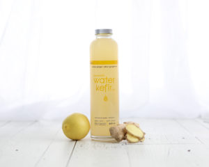 Mini lifestyle photo of lemon water bottle and ginger on white wood in front of white curtains