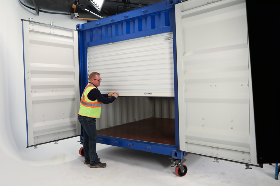 Lifestyle photo of man in yellow vest closing roller door of a blue steel box