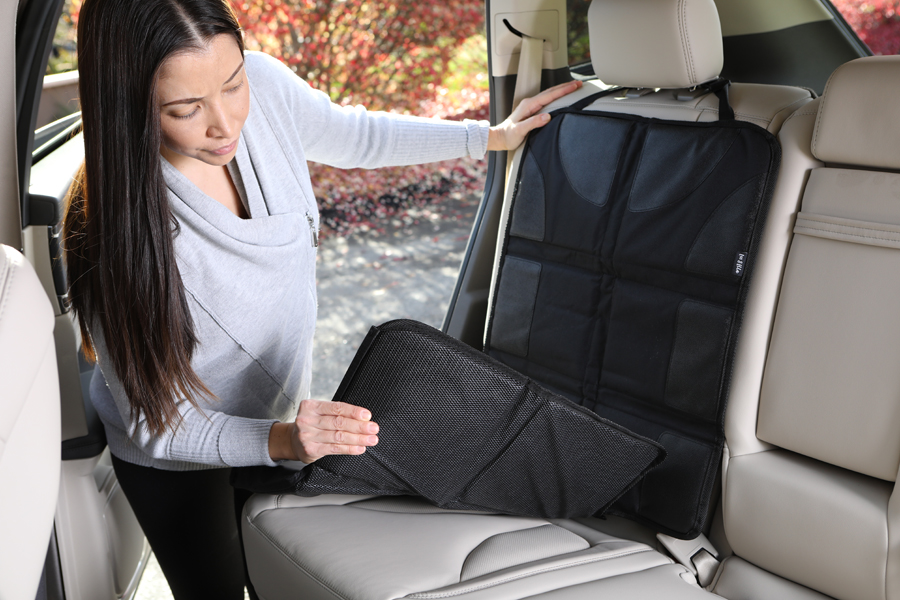 Product photo of woman wearing grey demonstrating baby car seat mat