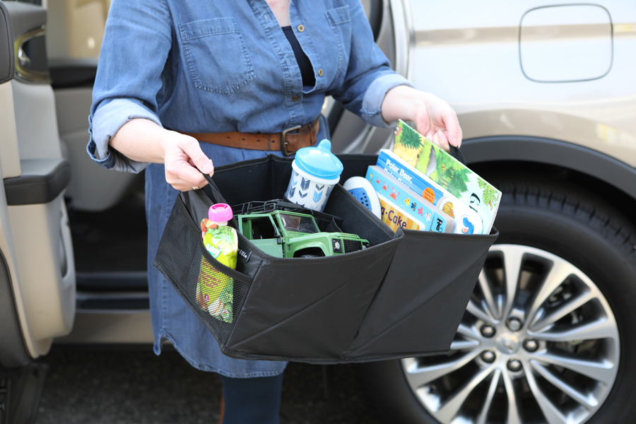 Lifestyle photo of woman caring baby car product box of toys in front of car