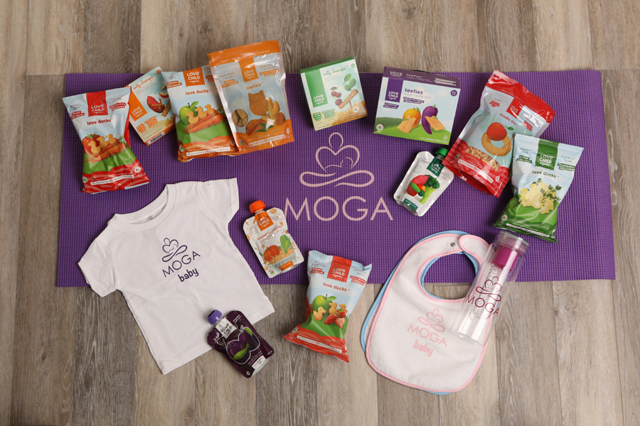 moga mini lifestyle photo of a purple yoga mat on wood floor with baby products