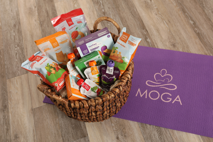 Mini lifestyle photo of basket of baby snacks and drinks on a purple yoga mat on a wood floor