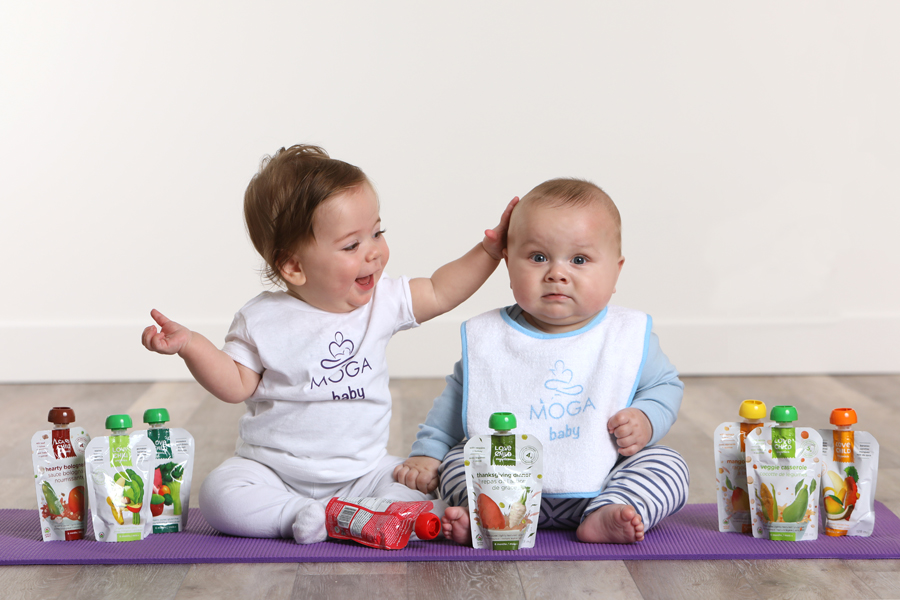 Lifestyle photo of 2 babies sitting on a purple yoga mat with baby snacks and drinks