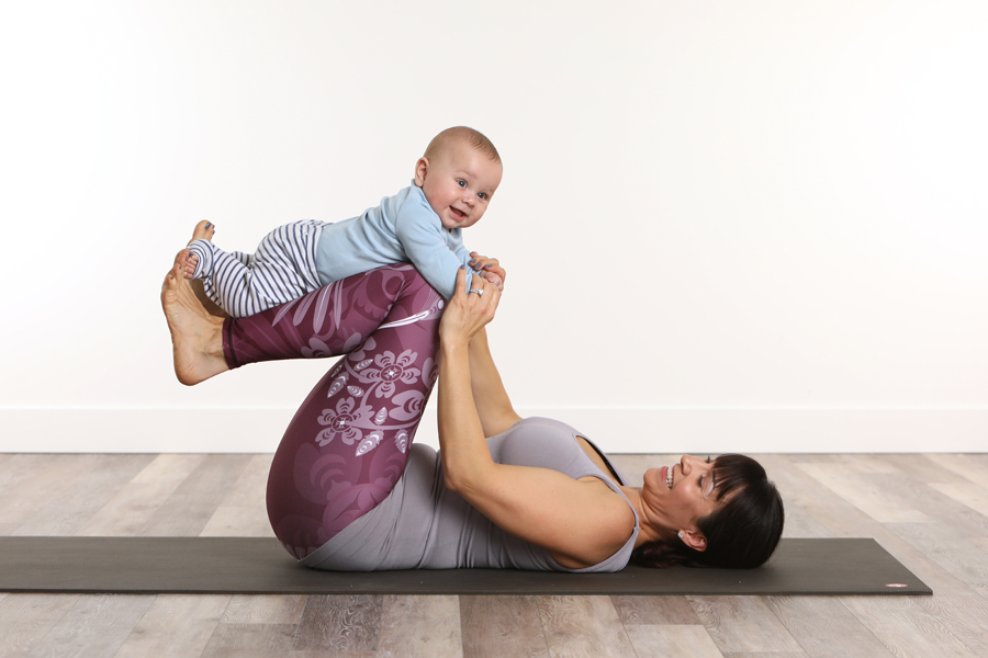 lifestyle photo of mother in yoga pants holding baby on legs while lying on a black yoga mat