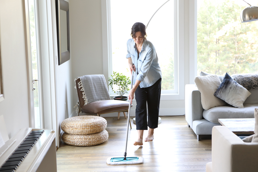 Lifestyle photo of woman in a denim shirt mopping a living room hard wood floor